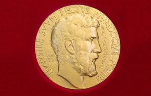 A gold disc or medal with a bearded man's portrait.