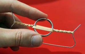 A wire and rubber band contraption that is being wound up.