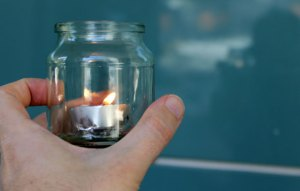Image of a tea light in a small glass jar.