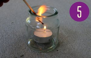 Image of a match lighting a tea candle in a small glass jar.