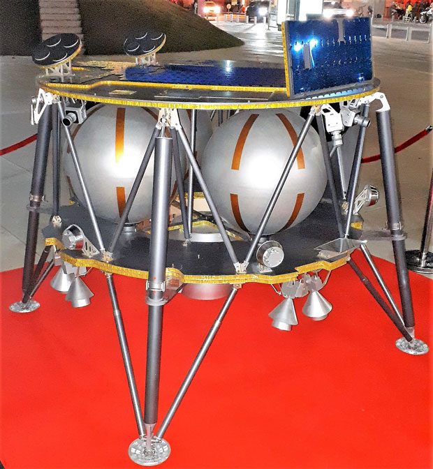 Circular table like spacecraft with metal legs and spheres sandwiched between the circular panels.