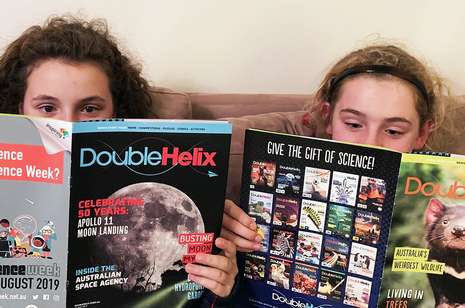 Two girls reading Double Helix magazine