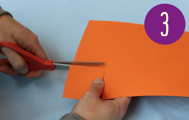 Cutting orange card with scissors.