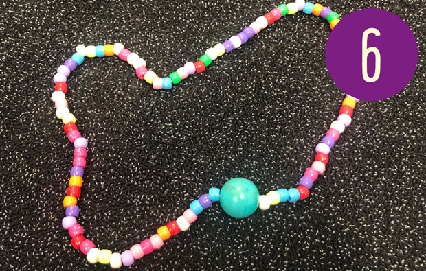 A string of colourful beads with one larger bead.