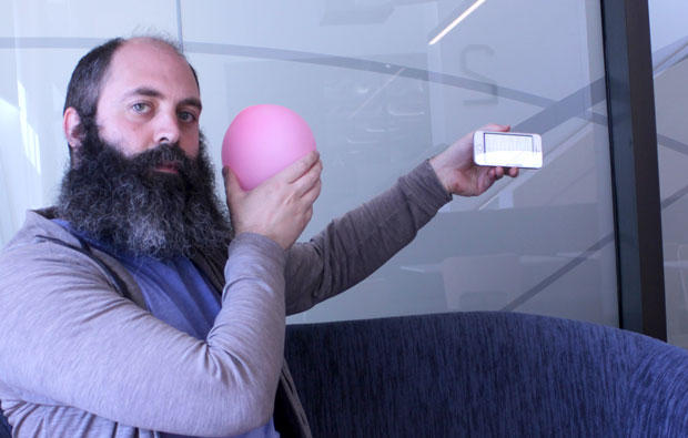 A man holdiing a pink baloon near his face and a phone at arms length.