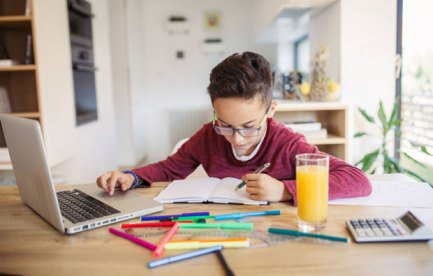 Picture of a child working at a desk with pen and paper and laptop.