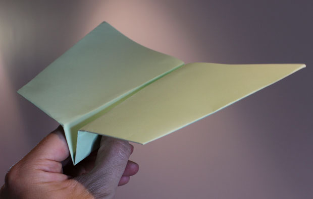 Hand holding a folded paper plane.