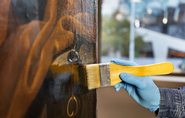 Gloved hand painting varnish with a brush onto a work of art.