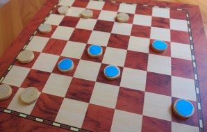 Image of a chess board with some blue and some white tokens.