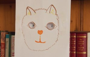 Drawing of a cat with cut out eyes.