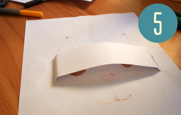 Placing the slightly bent strip of paper behind the cut out eyes.