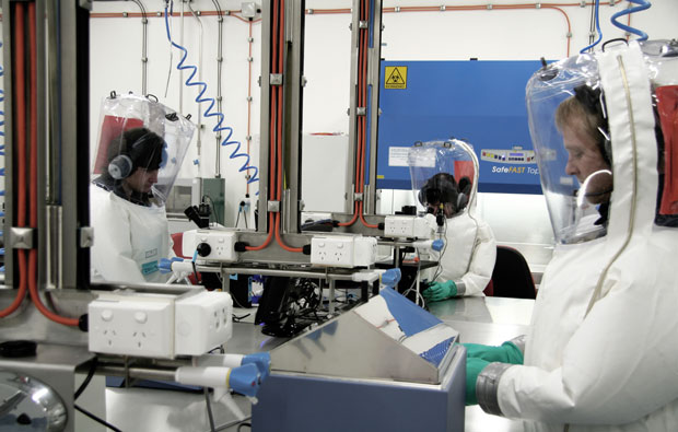 Several scientists wearing protective suits in a lab