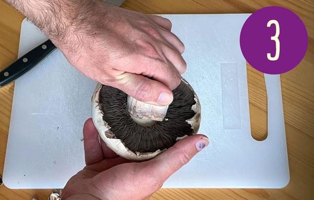Pulling off the stem of the mushroom.