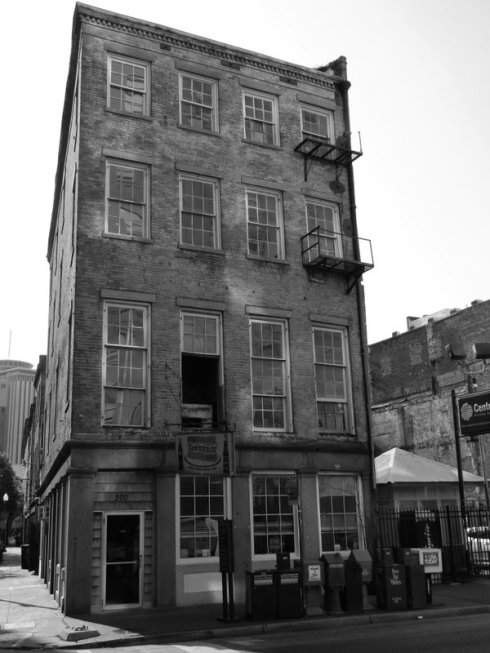 black and white photograph of a narrow, four story brick building missing a window