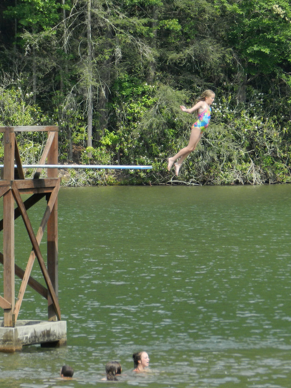 photograph of a girl jumping off the high dive at a lake