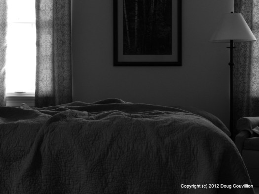 still life black and white photograph of an unmade bed in the early morning light