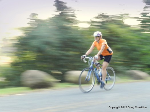 Photograph of a smiling woman cycling