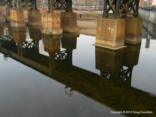 photograph of a railroad bridge reflected in the James River Canal Walk in Richmond, VA