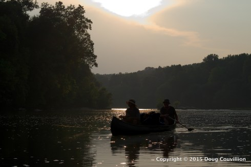 photograph of the silhouette of two men paddling a canoe on the Rappahannock River in Virginia
