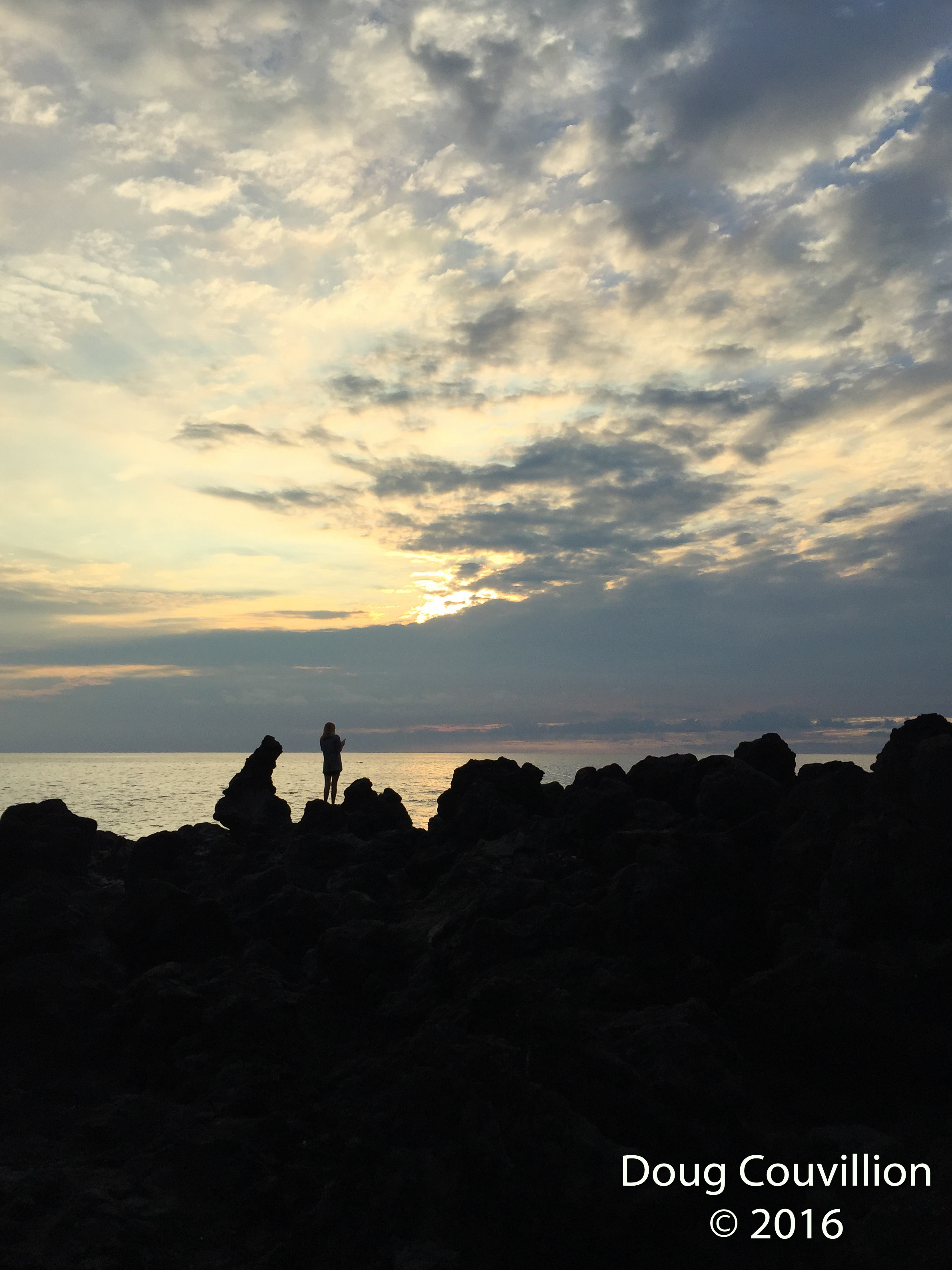Photograph by Doug Couvillion: silhouette of a person standing on the Kona shore at sunset