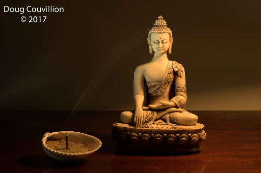 photograph of a Buddha statue and incense by Doug Couvillion