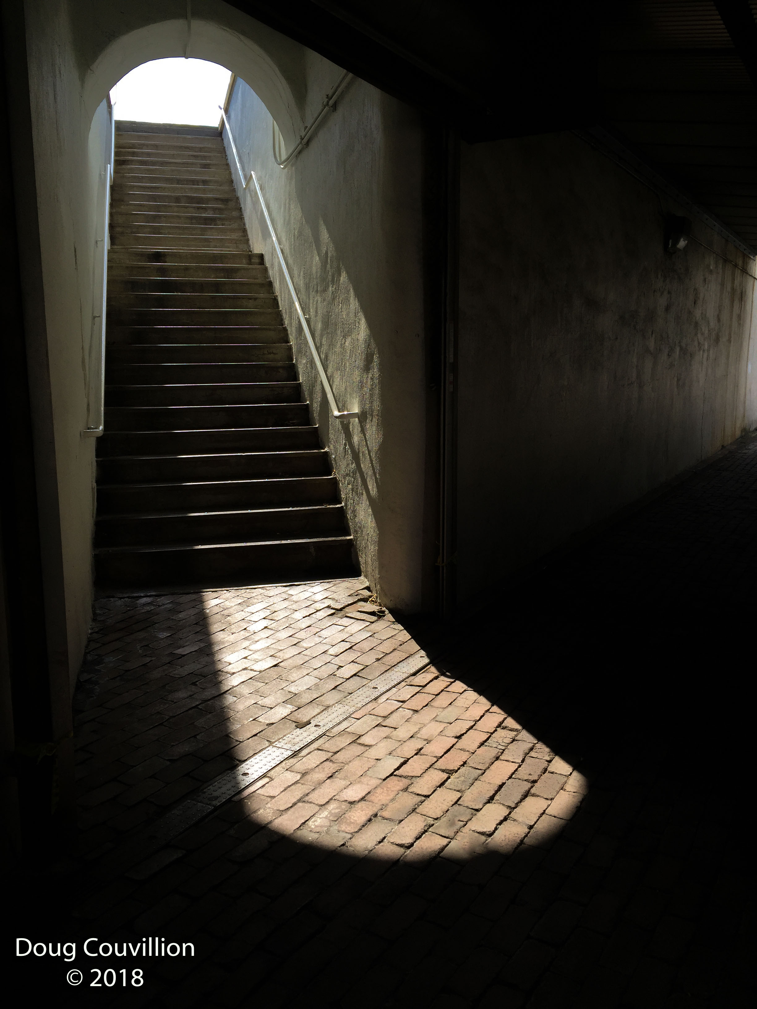 Photograph of stairs leading from a dark walkway into the bright light by Doug Couvillion