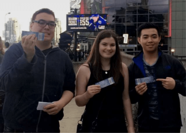3 students downtown holding up their Drake tickets