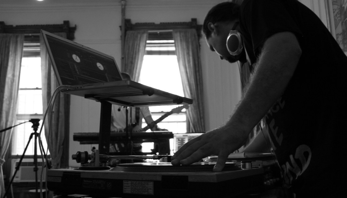 Black and white image shows Music Technology instructor Kayvon Sarfehjooy bent over turntables with headphones around his neck.