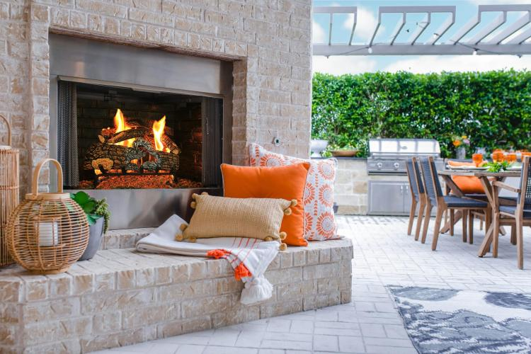 The Elmsdale outdoor living area featuring a built-in fireplace and outdoor kitchen by Drees Homes