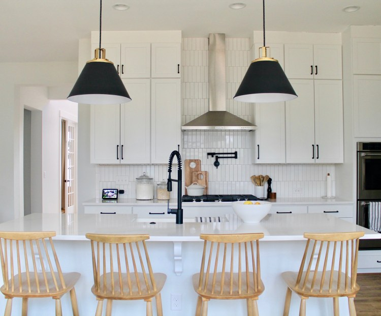 Interior Designer Hannah French's White Kitchen Featuring Black Light Pendants, an Enormous Island and Pot Filler | By Drees Homes in Raleigh, North Carolina