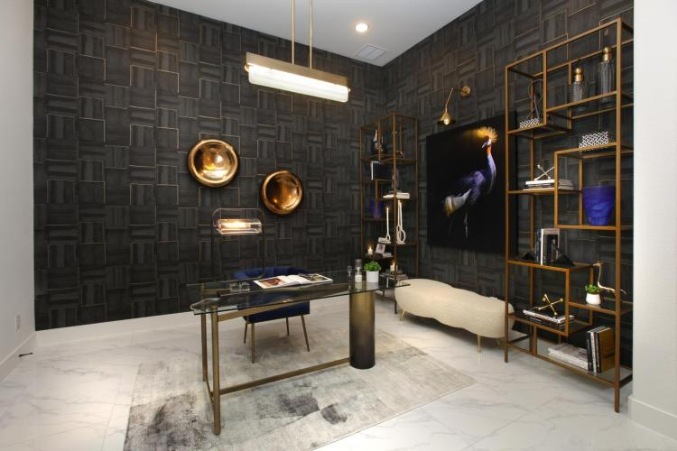 Study in new home featuring black textured wallpaper, brass lighting and a desk   Room by Drees Custom Homes