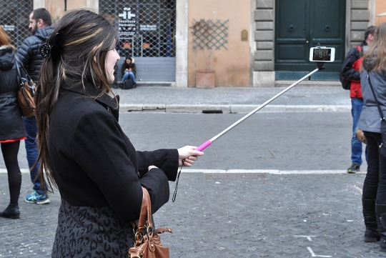 A woman uses a 'selfie stick' to take a selfie. (click for credit)