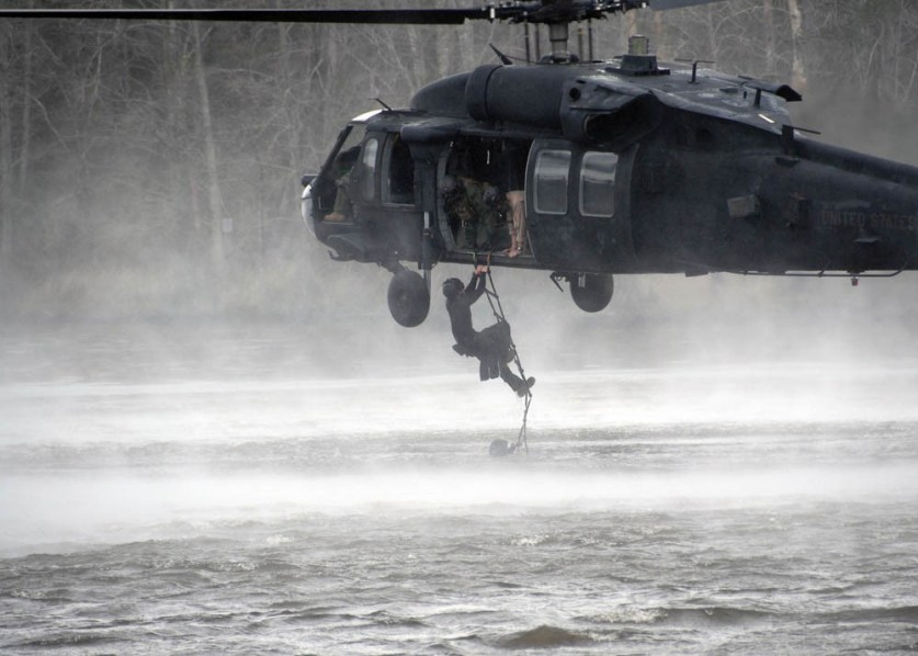 080220-N-4500G-095 STENNIS SPACE CENTER, Miss. (February 20, 2008) -- A Special Warfare Combatant-craft Crewman (SWCC) assigned to Special Boat Team 22 (SBT-22) climbs a ladder up to an Army MH-60 Blackhawk helicopter from the 160th Special Operations Aviation Regiment during a cast and recovery exercise along the Pearl River. The special boat operators also jump from the helicopter and swim to a combat rubber raiding craft, which they then prepare to get underway. U.S. Navy photo by Mass Communication Specialist Robyn Gerstenslager.