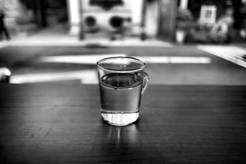 black and white photo of glass with water in it on a table