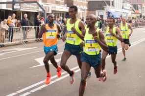 marathon runners with yellow tank tops wearing bib numbers