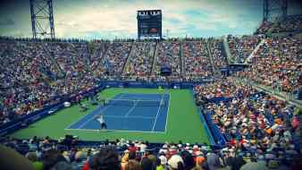 tennis match in an arena with large crowd