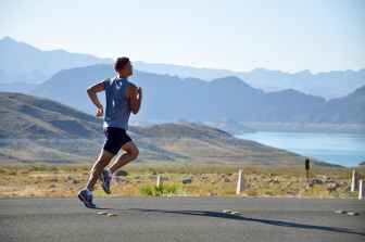 man running in shorts and tank top with headband near lake with mountains