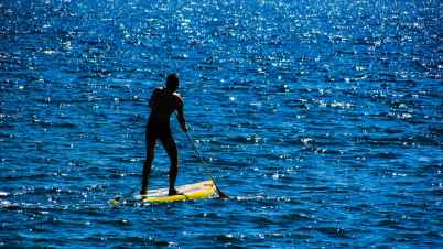 guy stand up paddle boarding on the ocean