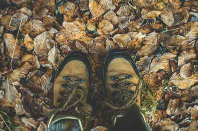 hiking boots on brown leaves outside