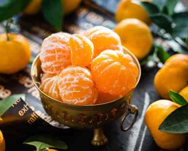 peeled clementines in a metal bowl