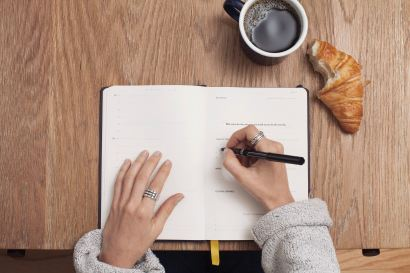 female arms writing in journal with coffee and croissant