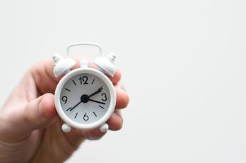 tiny alarm clock in a hand