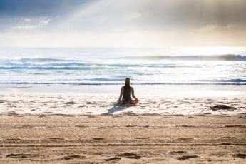 female mediating on the beach at the ocean