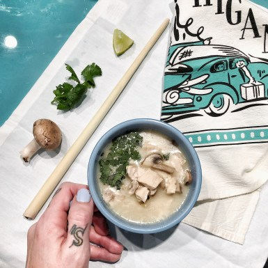 thai chicken coconut soup in blue bowl with hand