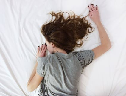women in gray shirt sleeping face down on white bedding