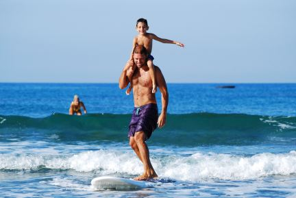 dad with son on shoulders surfing