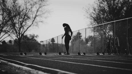female sprinter at track, black and white