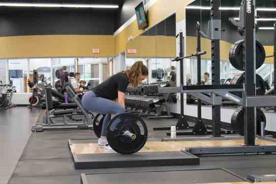 women in gym performing deadlift with barbell
