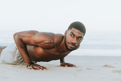 man performing burpees in the sand