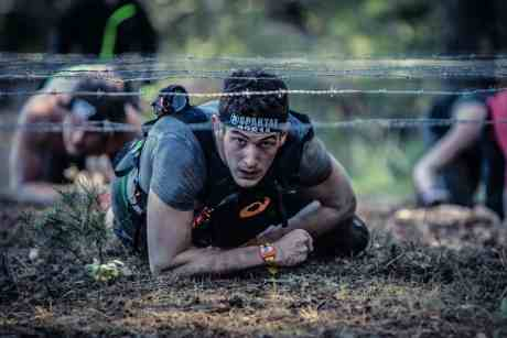 spartan race, man crawling under barbed wire